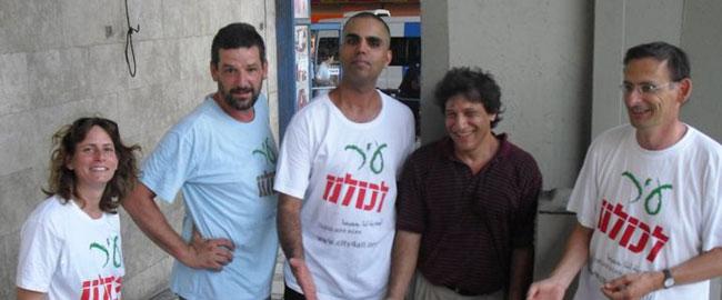 """פעילי """"עיר לכולנו"""" בדוכן שהקימו ליד התחנה המרכזית בתל-אביב, ראשון מימין: ח""""כ דב חנין (צילום: עיר לכולנו) 2013 ir-lekulanu"""