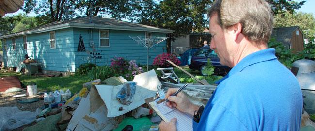 """הריסות בית בירוקרטיה מזכירה רשימות ארה""""ב בFEMA_-_44902_-_SBA_Specialist_writing_on_a_clipboard_in_Iowa"""