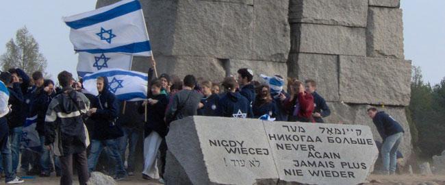 בני נוער מניפים דגלי ישראל בטרבלינקה בעת המסע לפולין שואה יום הזכרון masapolin
