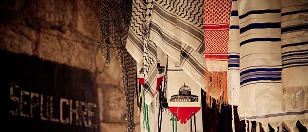 טליתות וכאפיות בעיר העתיקה בירושלים. מאחור: שלט המכוון לכנסיית הקבר יהדות נצרות איסלאם ישראל דת ערבים יהודים ירושלים העיר העתיקה Talit_Keffiyeh